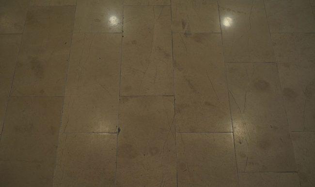 Pardoseală de marmură uzată ce prezintă zgârieturi, pete și ciobituri